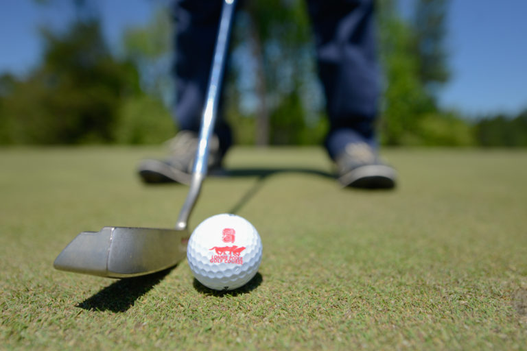 A golfer prepares to hit a golf ball with the Lonnie Poole Golf Course logo on it.