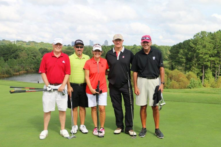 Participants in a golf outing pose for a photo.