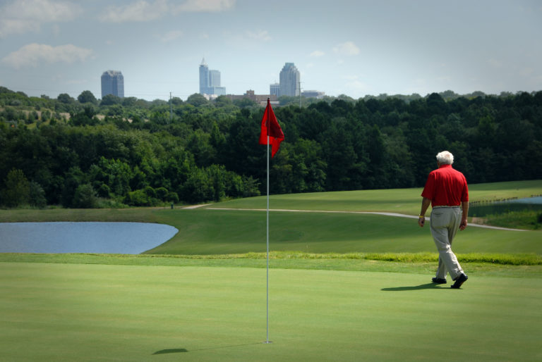Arnold Palmer walks on a green at NC State's Lonnie Poole Golf Course.