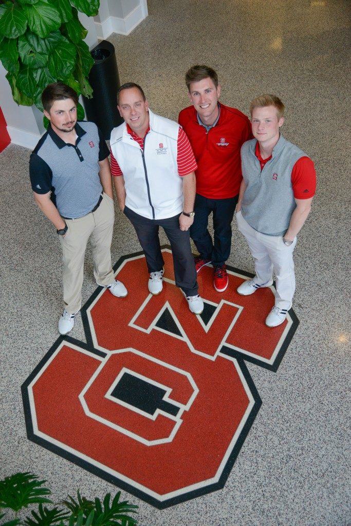 Player development staff standing on an NC State logo floor.