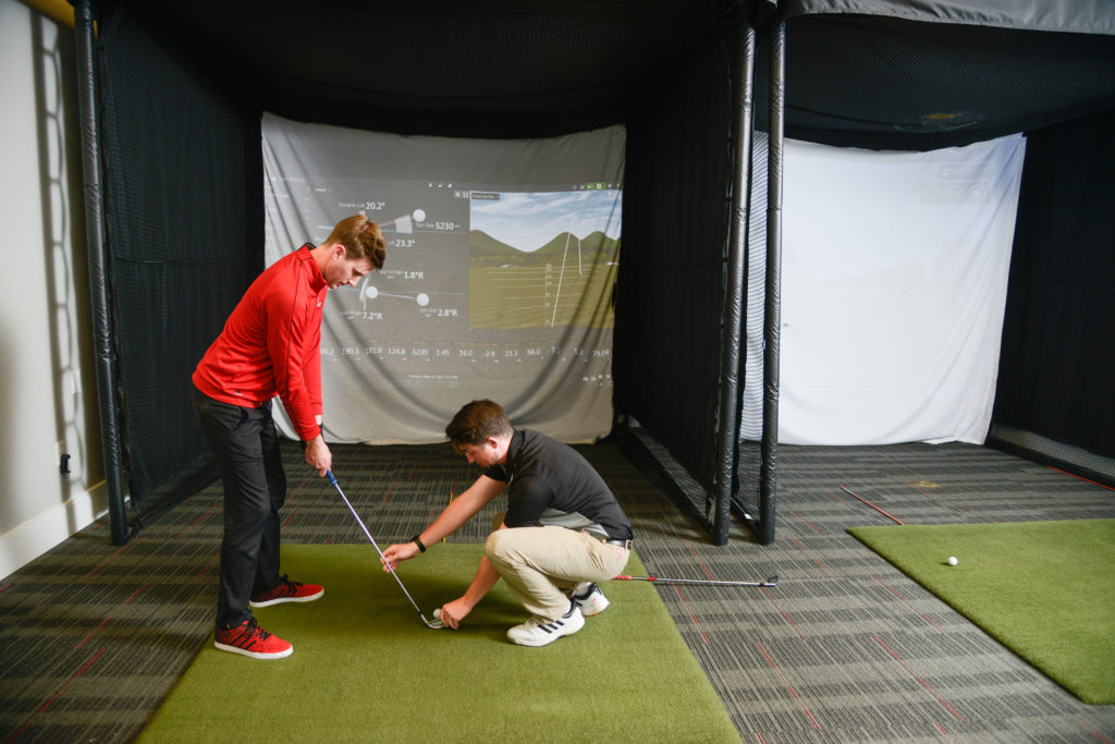 A golfer receives instruction from player development staff.