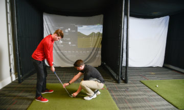 A golfer receives instruction from player development staff.