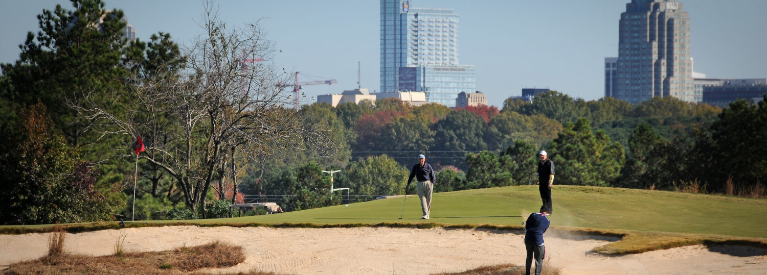Golfers in a sand trap, with the Raleigh skyline in the background.