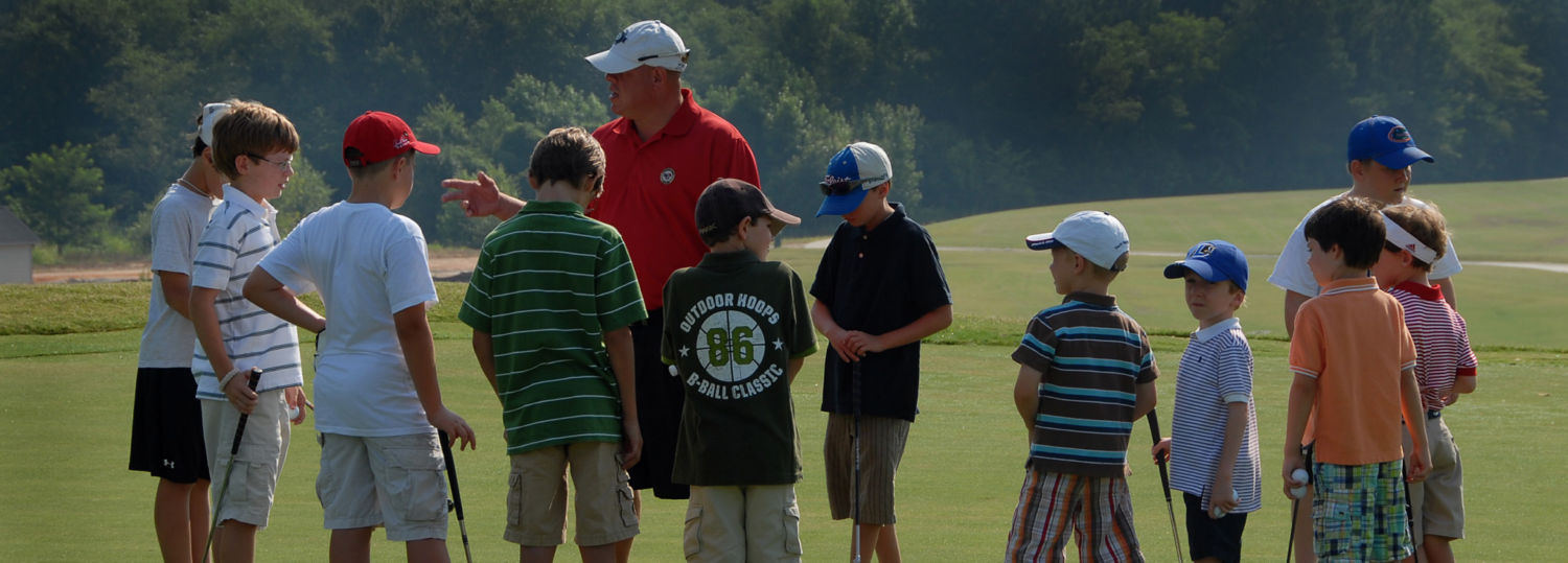 Young golf students listen to their instructor.
